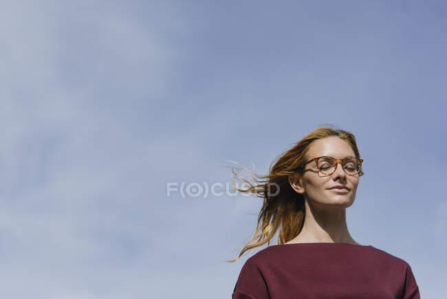 Porträt einer jungen Frau mit Brille und geschlossenen Augen unter blauem Himmel — Stockfoto