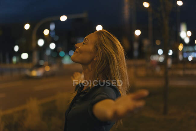 Young woman with outstretched arms in the city at night — Stock Photo