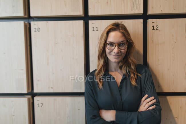 Ritratto di donna d'affari sicura in piedi agli armadietti — Foto stock