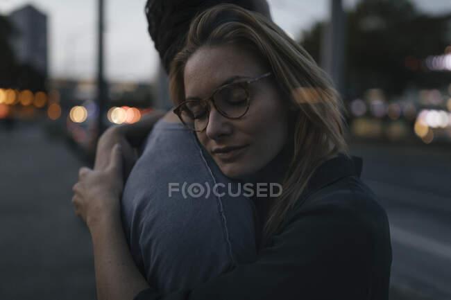 Pareja joven abrazándose en la ciudad al atardecer - foto de stock
