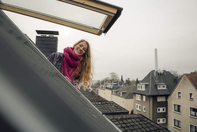 Glückliche junge Frau lehnt sich aus Dachfenster — Stockfoto