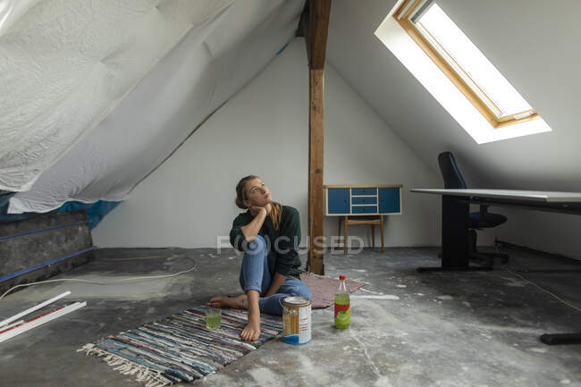 Молода жінка сидить на підлозі на горищі з відром для фарби. — стокове фото