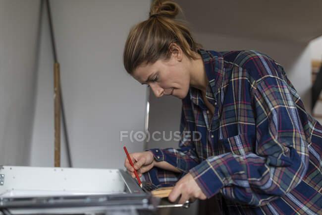 Jeune femme assemblant cuisine — Photo de stock