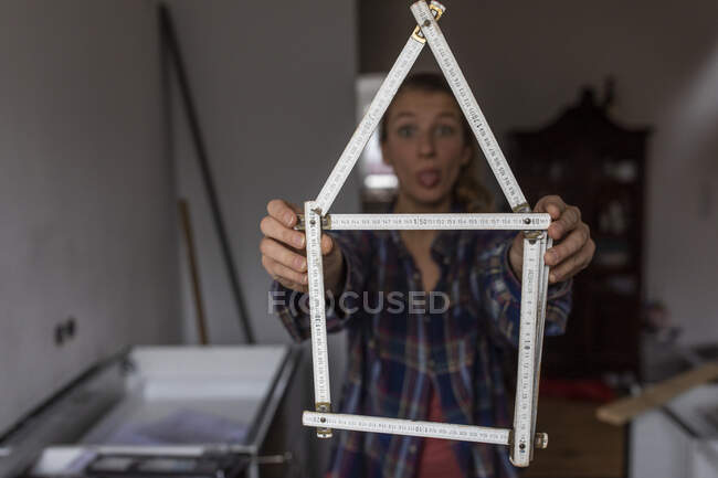 Playful young woman holding pocket rule in shape of a house — Stock Photo