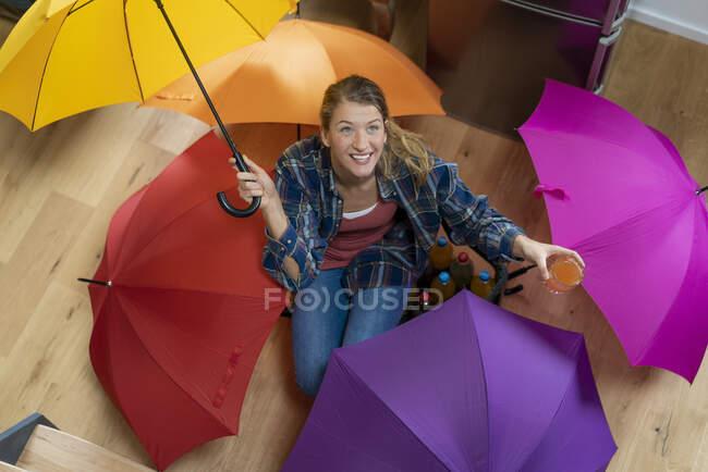 Jovem com guarda-chuvas sentados no chão — Fotografia de Stock