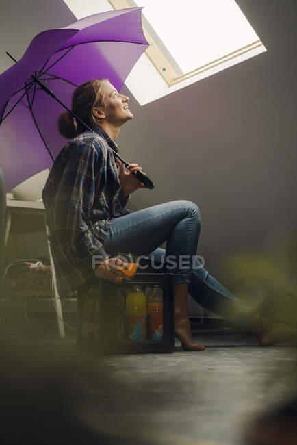 Sorrindo jovem mulher com guarda-chuva olhando pela janela — Fotografia de Stock