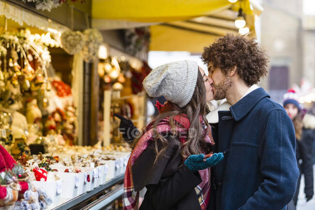 Feliz pareja joven cariñosa besándose en el mercado de Navidad - foto de stock