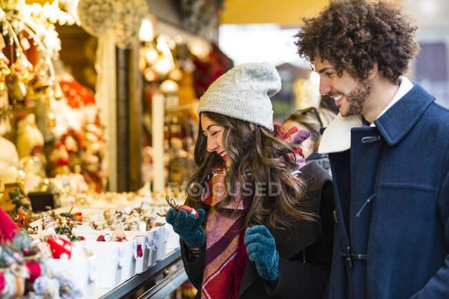 Pareja joven en un puesto en el mercado de Navidad - foto de stock