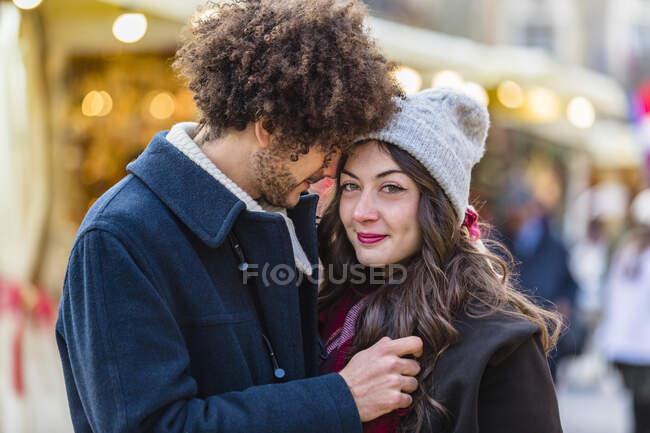 Feliz pareja joven y cariñosa en el mercado de Navidad - foto de stock