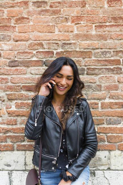 Ritratto di giovane donna con giacca di pelle nera, con smartphone, muro di mattoni sullo sfondo — Foto stock