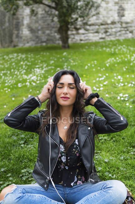 Giovane donna con le cuffie bianche, indossa giacca di pelle nera — Foto stock