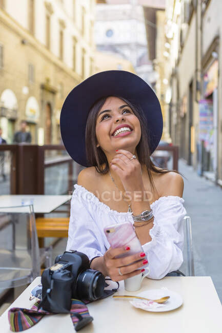 Italy, Florence, portrait of happy young tourist drinking espresso at pavement cafe — Stock Photo