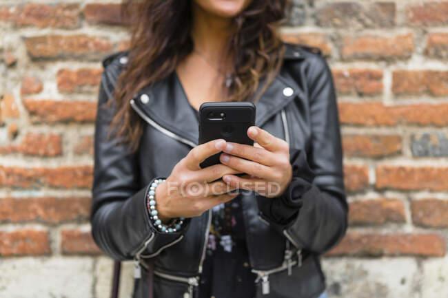 Giovane donna che indossa giacca di pelle nera, utilizzando smartphone, muro di mattoni sullo sfondo — Foto stock