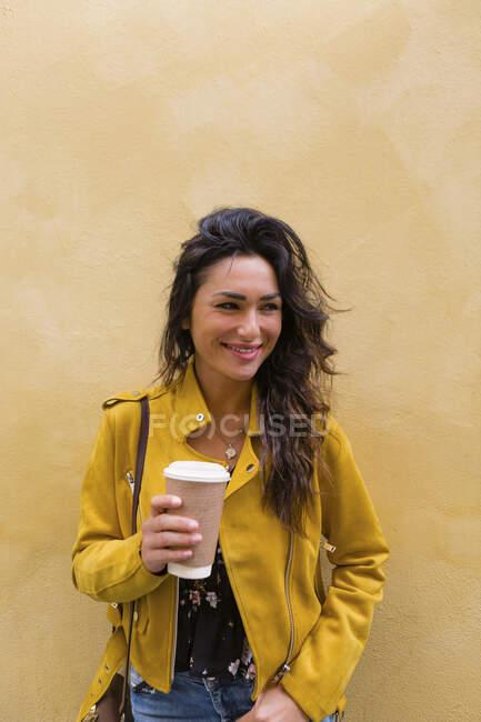 Ritratto di giovane donna che indossa una giacca di pelle gialla, con in mano una tazza di caffè — Foto stock