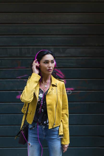 Ritratto di giovane donna con cuffie rosa, giacca di pelle gialla — Foto stock