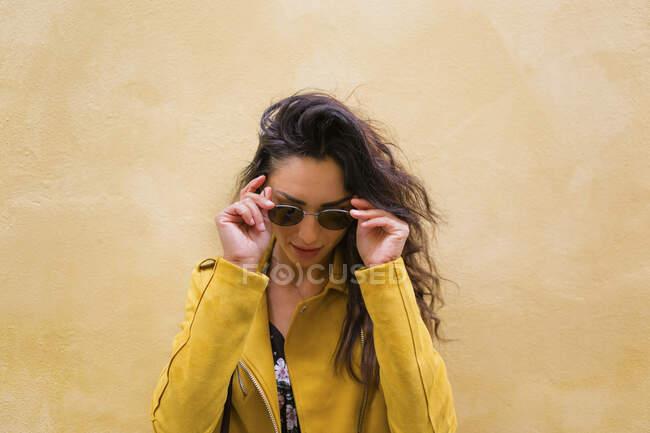 Ritratto di giovane donna con giacca di pelle gialla e occhiali da sole — Foto stock