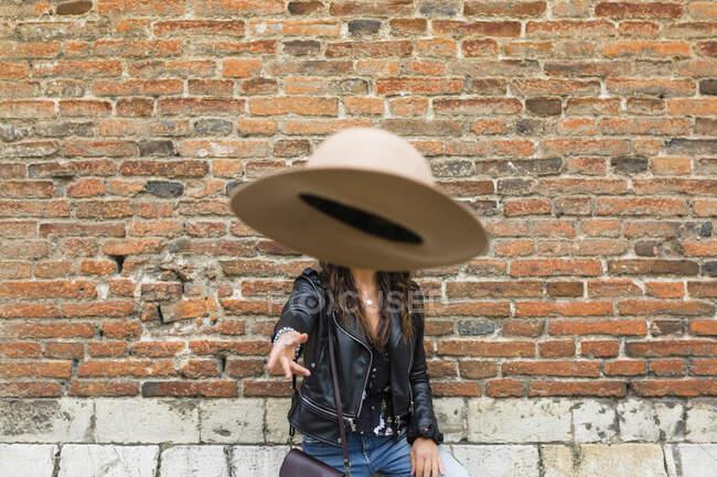 Ritratto di giovane donna con giacca di pelle nera, muro di mattoni, cappello da lancio — Foto stock