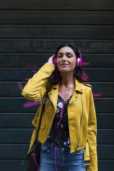 Ritratto di giovane donna con cuffie bianche, con giacca di pelle nera — Foto stock