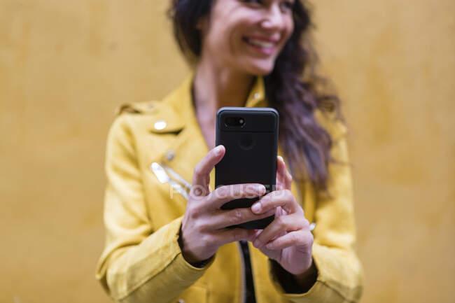 Ritratto di giovane donna che indossa giacca di pelle gialla e prende un selfie, parete gialla sullo sfondo — Foto stock