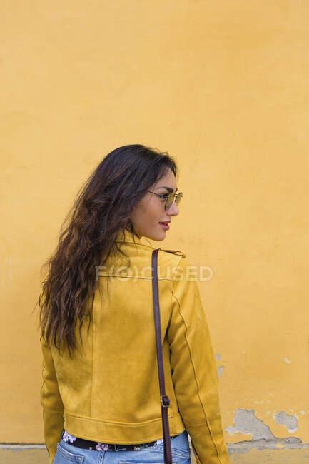 Ritratto di giovane donna con giacca di pelle gialla e occhiali da sole, vista posteriore — Foto stock