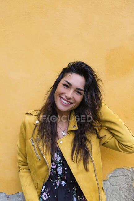 Ritratto di giovane donna con giacca di pelle gialla, mano nei capelli — Foto stock