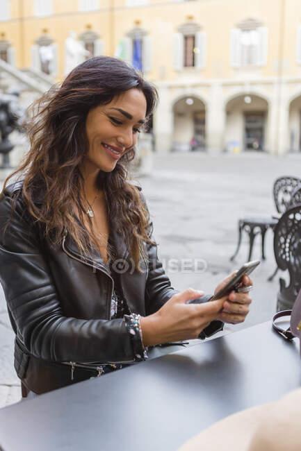 Giovane donna con tazza di caffè, utilizzando smartphone — Foto stock