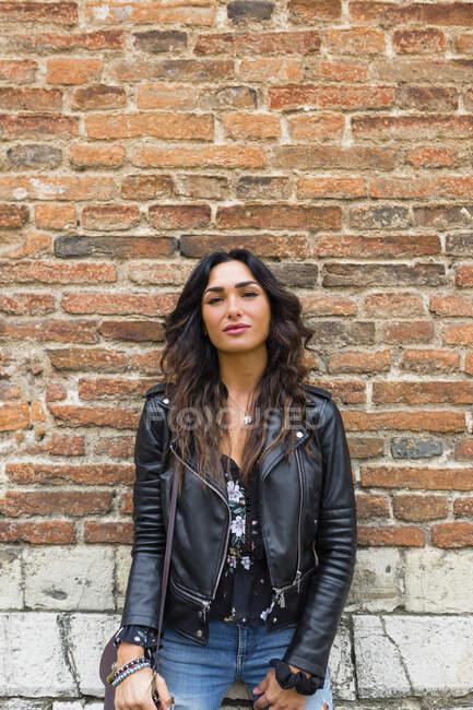 Ritratto di giovane donna con giacca di pelle nera, muro di mattoni — Foto stock