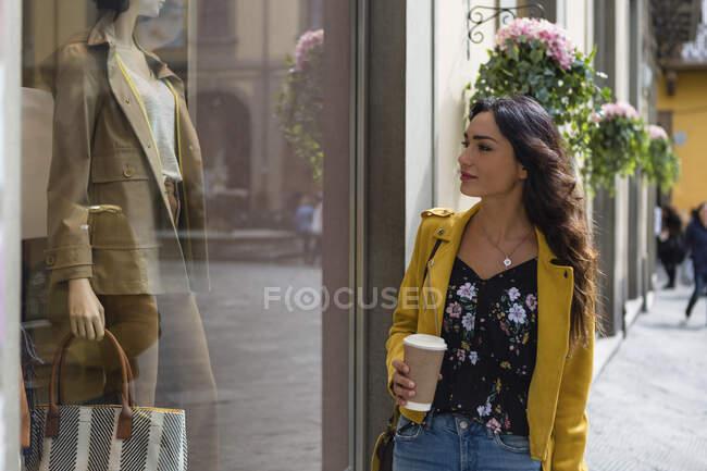Ritratto di giovane donna che indossa una giacca di pelle gialla, con in mano una tazza di caffè durante lo shopping — Foto stock
