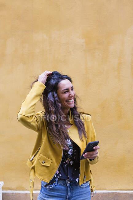 Ritratto di giovane donna ridente con giacca di pelle gialla e smartphone in mano — Foto stock