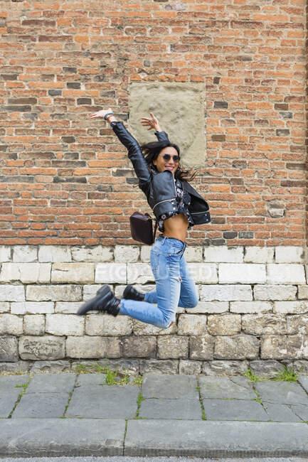 Giovane donna che salta in aria, muro di mattoni sullo sfondo — Foto stock
