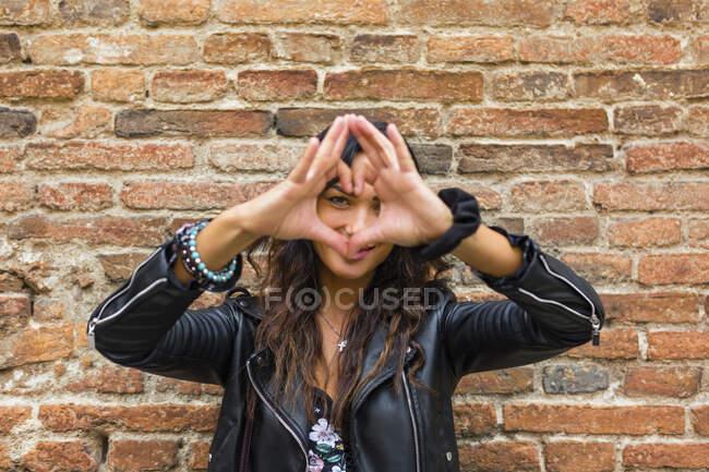 Ritratto di giovane che fa la forma del cuore con le mani e le dita, muro di mattoni — Foto stock