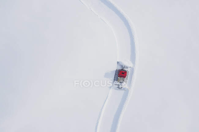 Austria, Tyrol, Galtuer, view to ski slope and snow groomer in winter, aerial view — Stock Photo