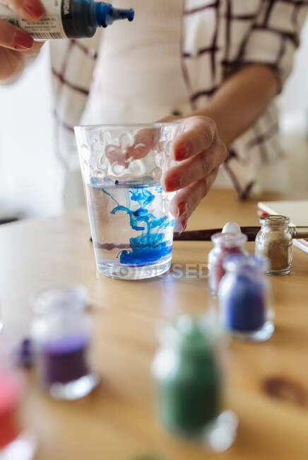 Painter filling liquid colour into glass of water, partial view — Stock Photo