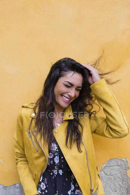 Ritratto di giovane donna ridente con giacca di pelle gialla, mano nella testa — Foto stock