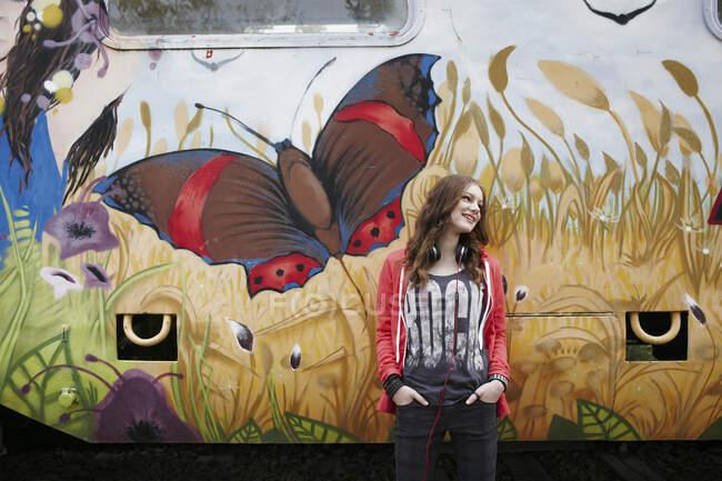 Sonriente adolescente de pie en un vagón de tren pintado - foto de stock