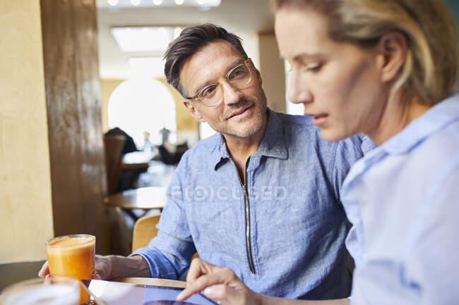 Hombre y mujer con la tableta en un café - foto de stock