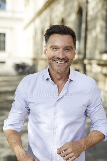 Retrato de hombre de negocios feliz en la ciudad - foto de stock