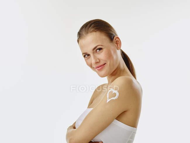 Mujer joven aplicando crema corporal, corazón sobre hombro - foto de stock