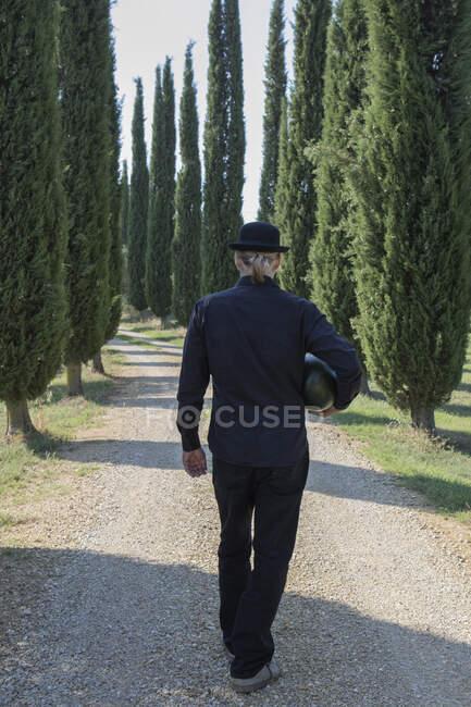 Italia, Toscana, vista trasera del hombre rodeado de cipreses con un sombrero de jugador de bolos sosteniendo un melón - foto de stock