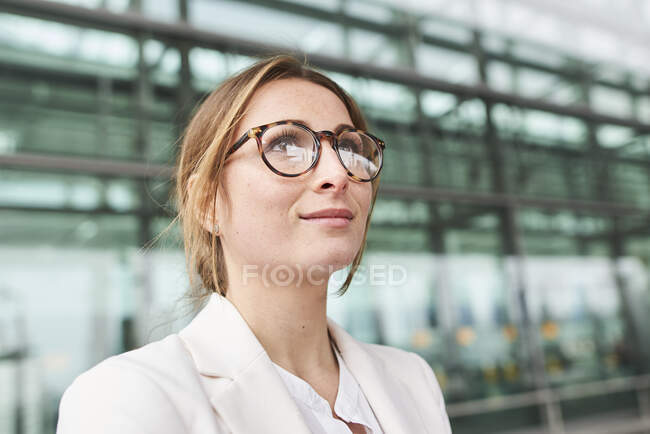 Portrait of young businesswoman wearing glasses in front of a building — Stock Photo