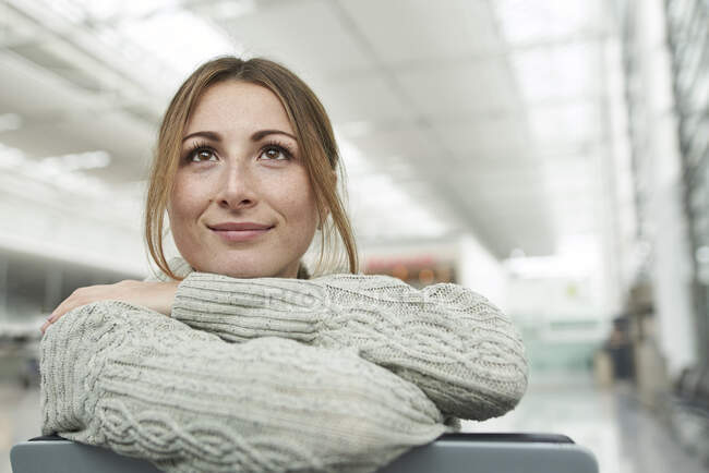 Portrait of smiling young woman at the airport sitting in waiting area — Stock Photo