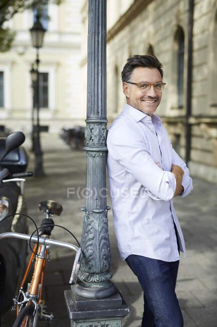Retrato de hombre de negocios sonriente con bicicleta apoyada contra poste de lámpara en la ciudad - foto de stock