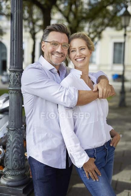 Retrato de pareja feliz abrazándose en la ciudad - foto de stock