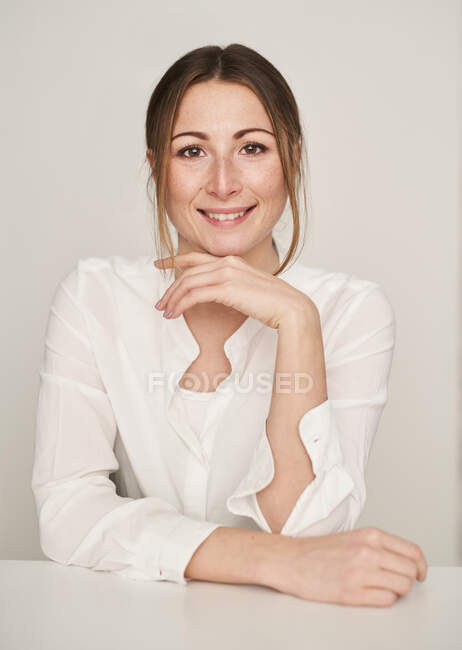 Portrait of smiling young woman wearing white blouse — Stock Photo
