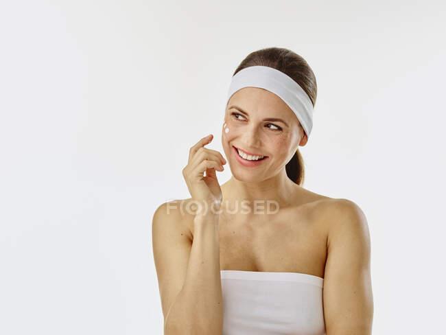 Mujer joven aplicando crema facial en su cara - foto de stock