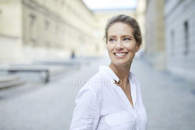 Retrato de una mujer sonriente con camisa blanca en la ciudad - foto de stock