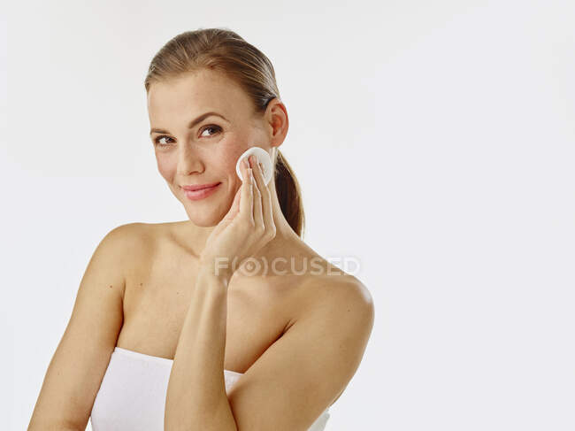 Mujer joven usando almohadilla de algodón - foto de stock