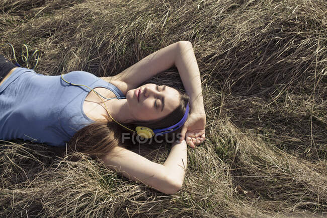 Relaxed young woman lying in meadow wearing headphones — Stock Photo