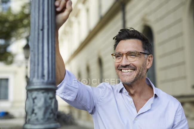 Retrato de hombre de negocios feliz apoyado contra poste de lámpara en la ciudad - foto de stock