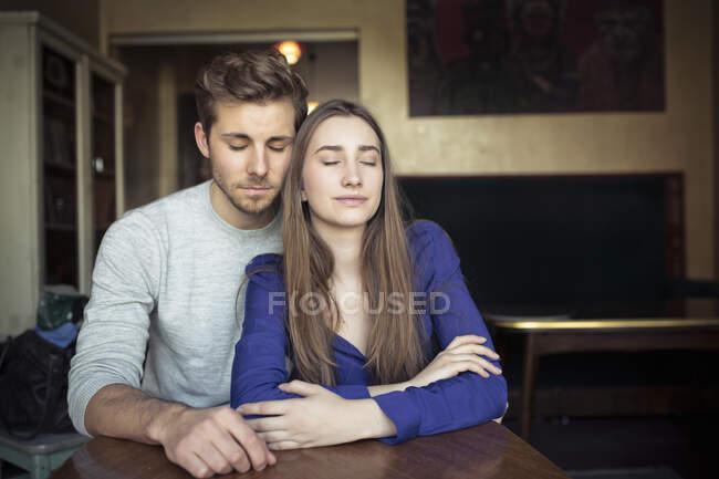 Retrato de pareja joven en un café con los ojos cerrados - foto de stock